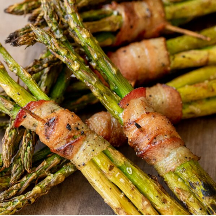 Small bundles of bacon wrapped asparagus stacked on a wooden board.