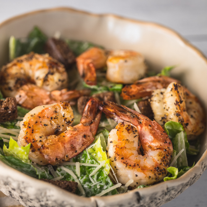 Lemon pepper grilled shrimp on top of a bed of lettuce with text overlay - Grilled Shrimp Caesar Salad.