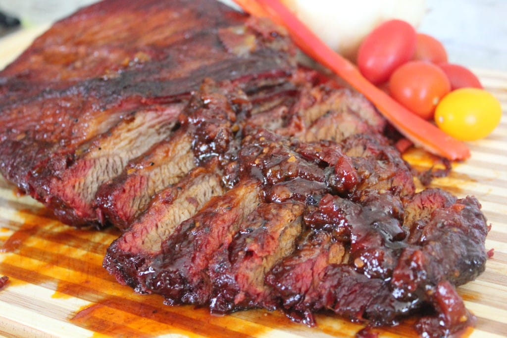Sliced smoked brisket arranged on a wood cutting board and topped with bacon BBQ sauce. Grape tomatoes in the background.