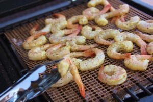 cooked shrimp on grill grate, one shrimp being held up by tongs