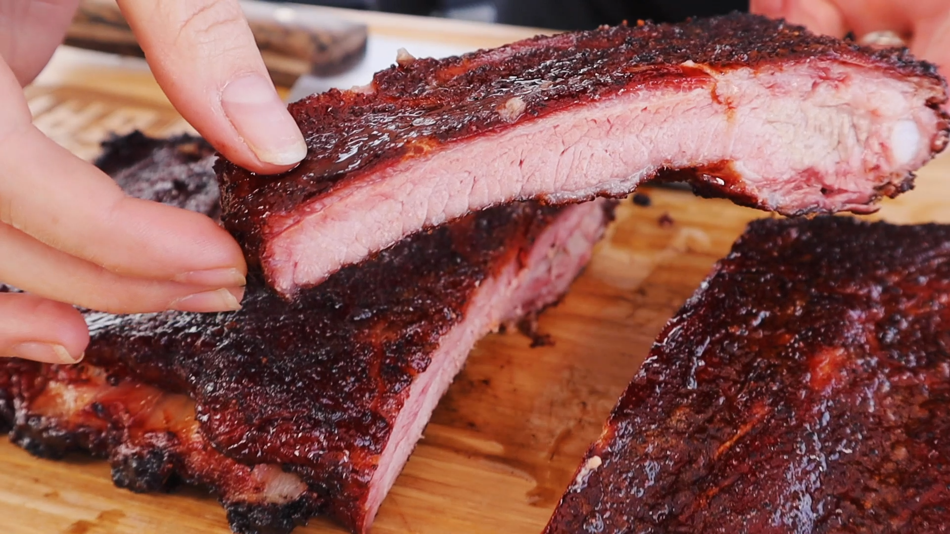 One low and slow rib held above a rack of low and slow ribs.