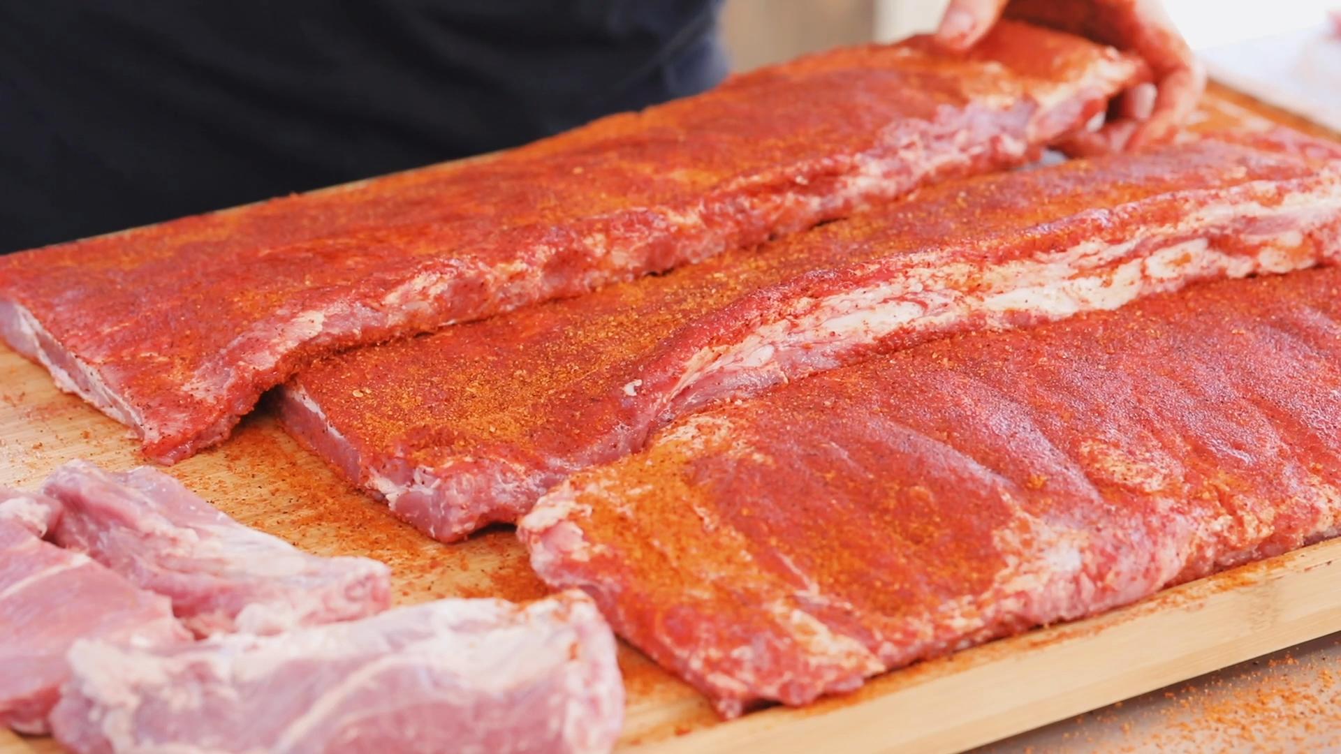 Three racks of seasoned ribs on a wooden cutting board.