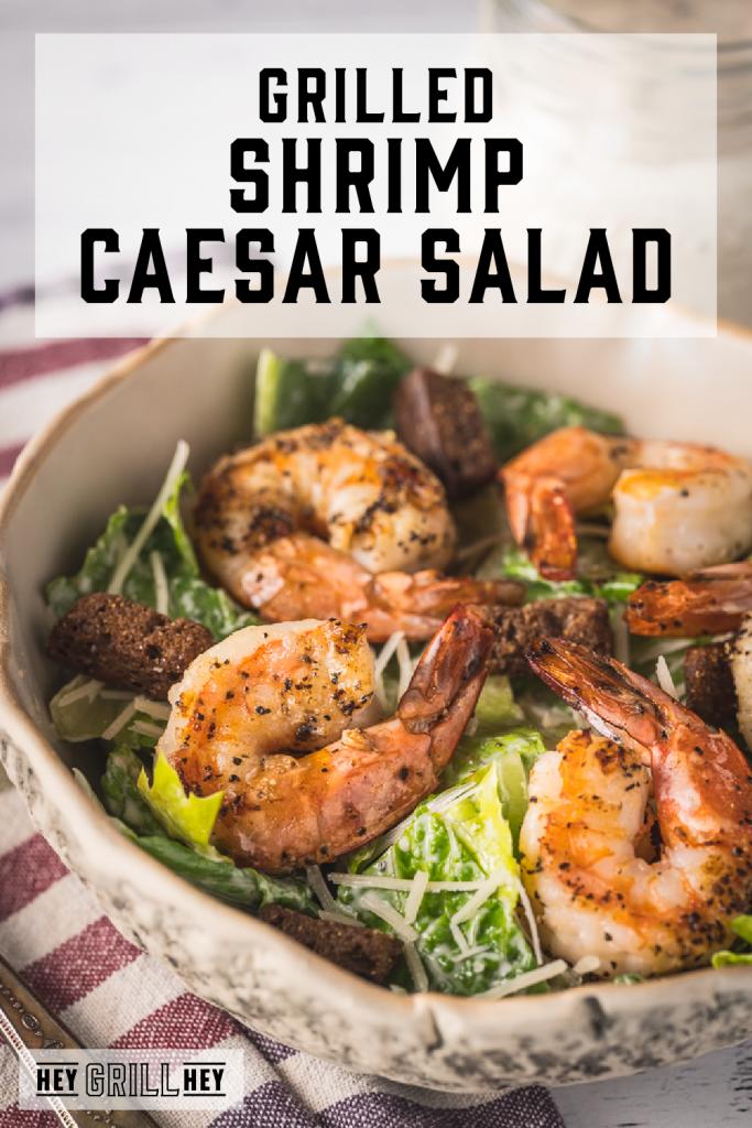 Lemon pepper grilled shrimp on top of a bed of lettuce with text overlay - Grilled Shrimp Caesar Salad.