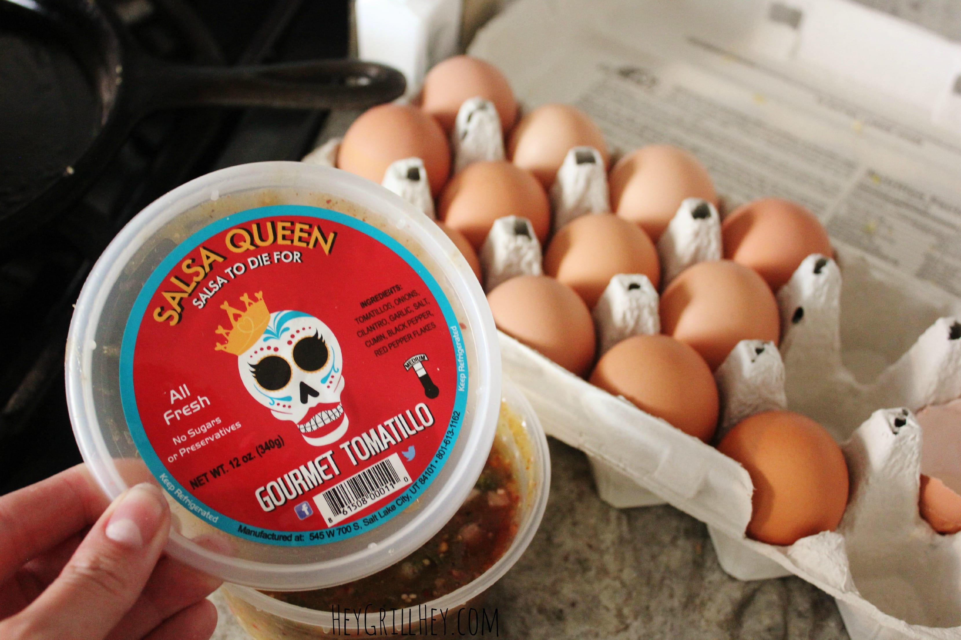 A bowl of salsa next to an open carton of brown eggs.