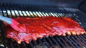 full rack of ribs on grill grate inside of grill, being brushed with barbeque sauce