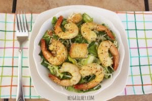 a white bowl full of green salad, topped with 6 cooked shrimp arranged in a circle