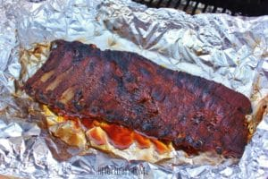 full rack of fully cooked ribs atop a sheet of aluminum foil and a small amount of liquid