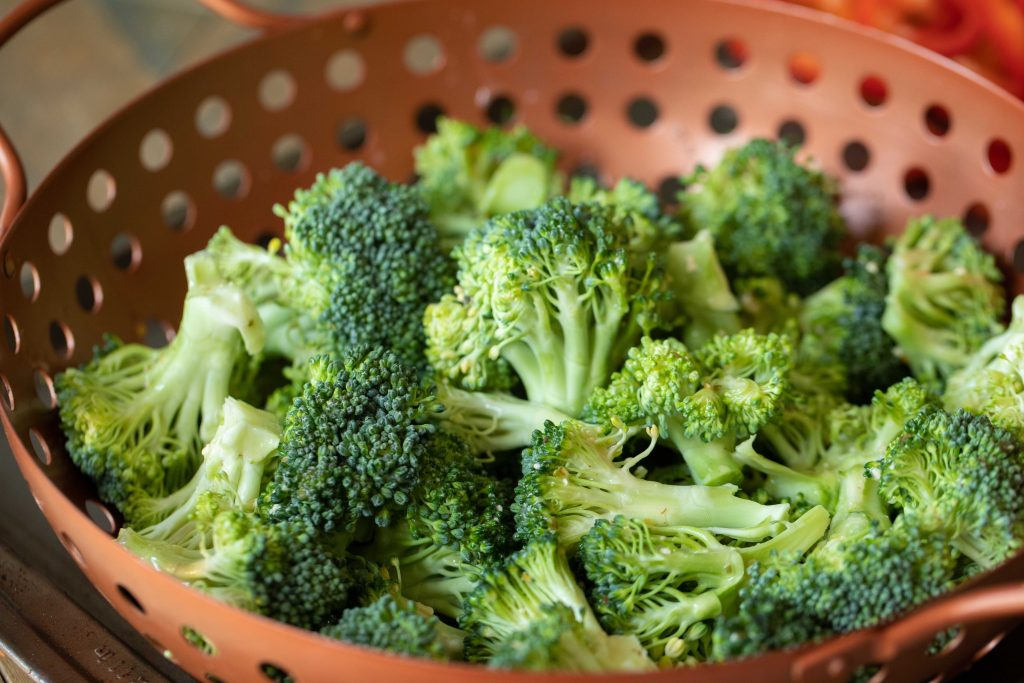 Raw broccoli florets in a copper vegetable basket.