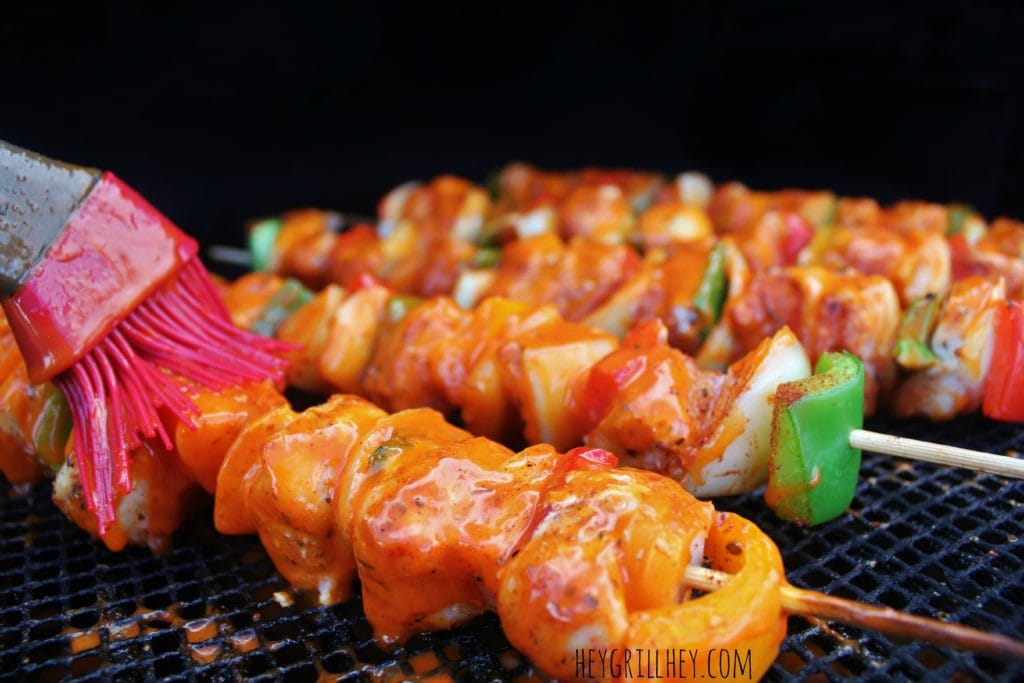 close up shot of cooked and cubed chicken and peppers on the grill grate being brushed with BBQ Sauce