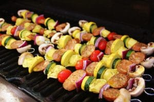 metal skewers filled with alternating chopped and uncooked pieces of mushroom, purple onion, tortellini pasta, sausage, yellow squash, zucchini, and cherry tomato, all arranged in a line on a grill grate inside the grill
