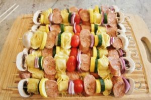 metal skewers filled with alternating chopped and uncooked pieces of mushroom, purple onion, tortellini pasta, sausage, yellow squash, zucchini, and cherry tomato, all arranged in a line on a wooden cutting board