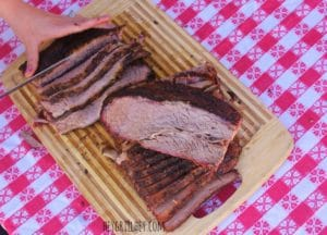 Fully cooked brisket resting on a wooden cutting board and being sliced into half inch thick slices