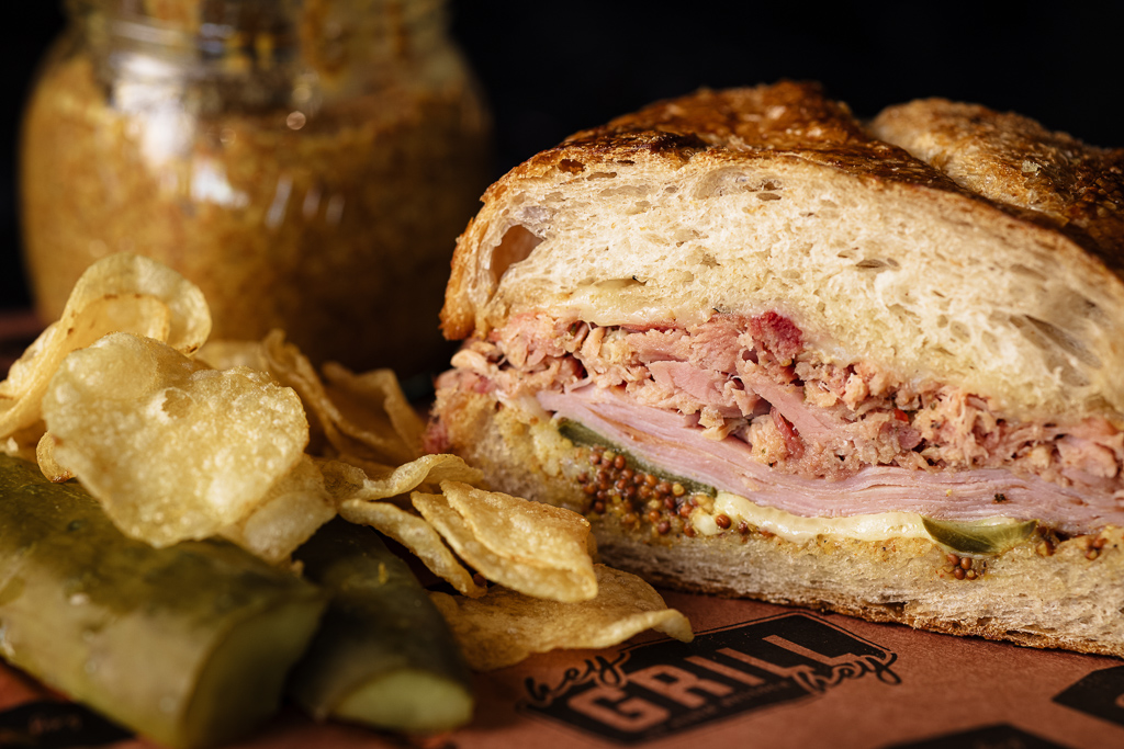 Cuban sandwich on peach butcher paper next to potato chips and a jar of spicy mustard.