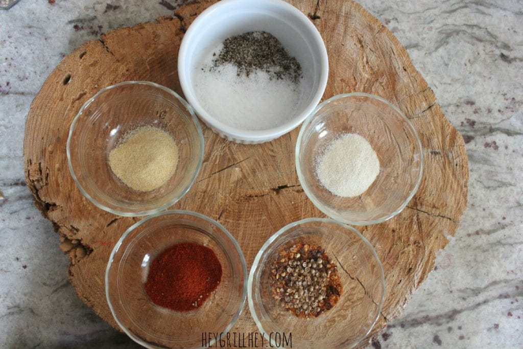 Ingredients in small bowls arranged on a wood cutting board.