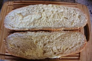 French bread sliced in half long-ways and topped with a layer of butter on each slice of bread