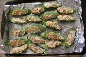 Raw Jalapenos, sliced in half longways and cored and filled with a mixture of cheese, sausage, and white sauce- arranged in a single layer on a baking sheet covered in aluminum foil