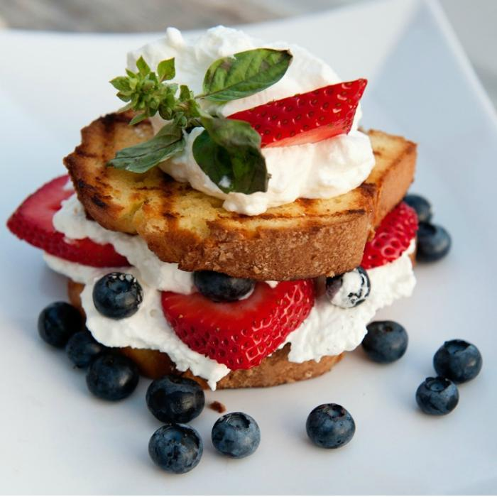 stacked layers of grilled lemon cake, strawberries, blueberries, and whipped cream served on a white plate