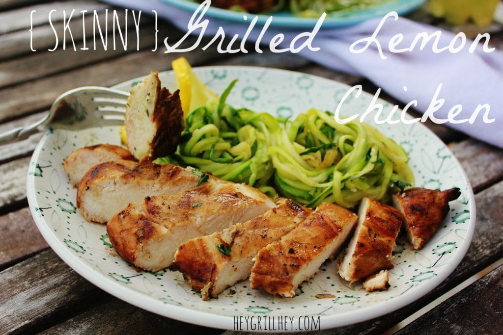 Sliced grilled chicken breasts on a white and blue plate with zucchini noodles