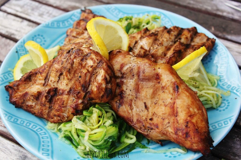 Four grilled chicken breasts on a blue plate with zucchini noodles and lemon slices