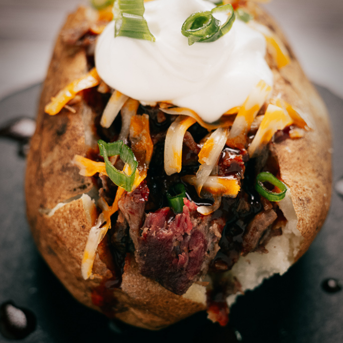 Brisket stuffed baked potato topped with shredded cheese and sour cream.
