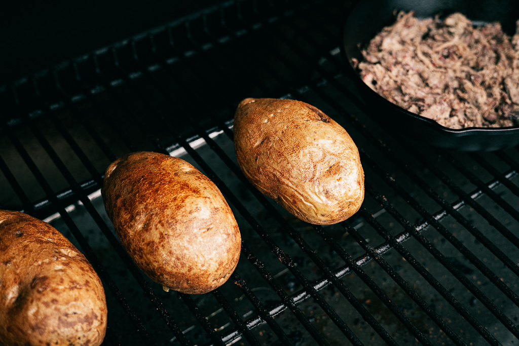 Whole russet potatoes in a BBQ grill next to a cast iron skillet of brisket.
