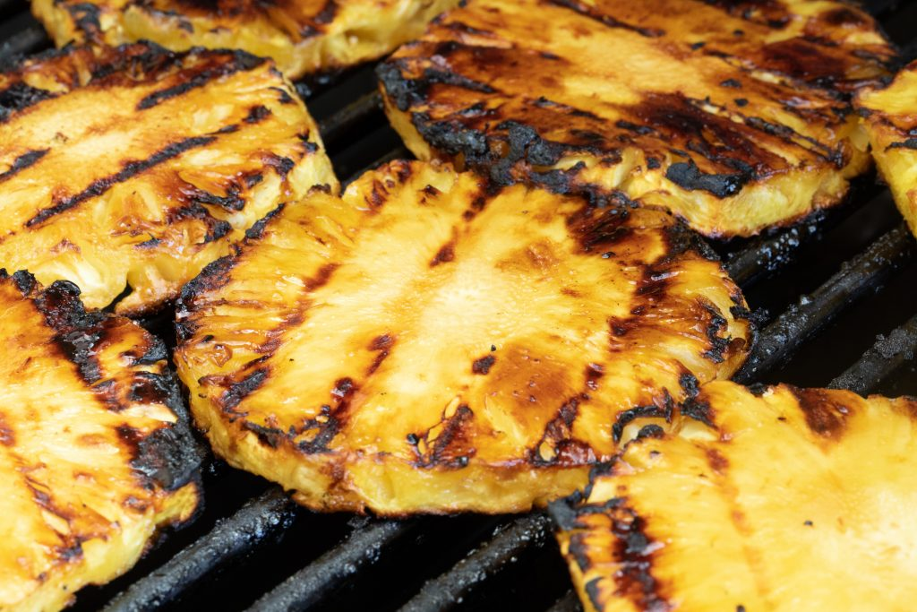 Grilled pineapple with dark grill marks on grill grates.