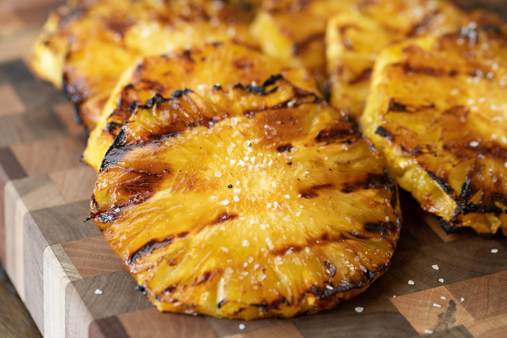 Grilled pineapple with grill marks on a wood cutting board.