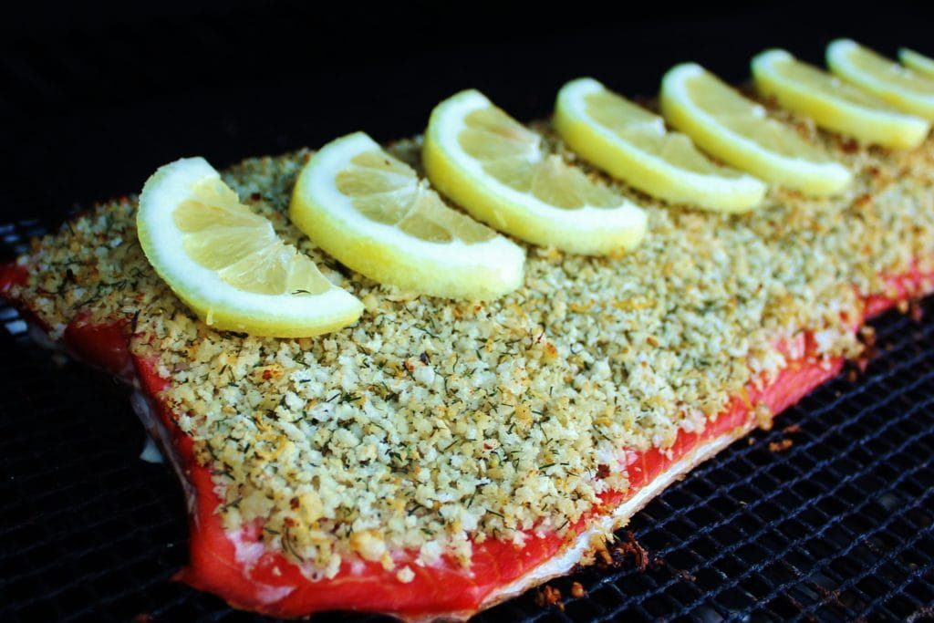 Close up view of salmon topped with seasoning and lemon slices, and resting on a grill grate.