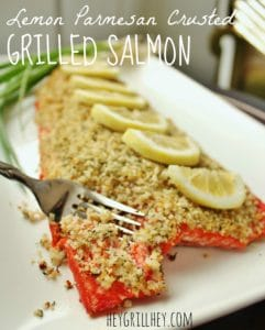 Cooked salmon topped with parmesan cheese, lemon slices, and served on a white plate