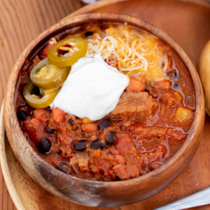 Wooden bowl of brisket chili topped with shredded cheese, sliced peppers, and a dollop of sour cream.