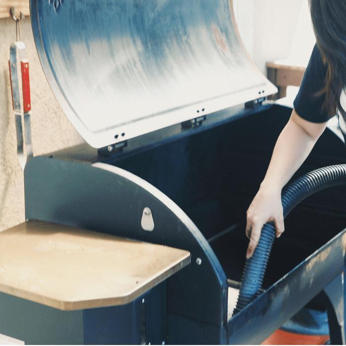 woman vacuuming interior of a pellet smoker