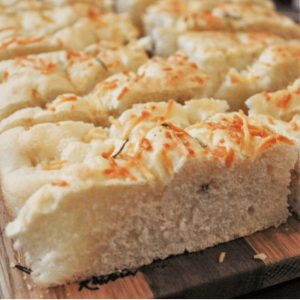 rosemary parmesan focaccia bread sliced and served on a wood platter