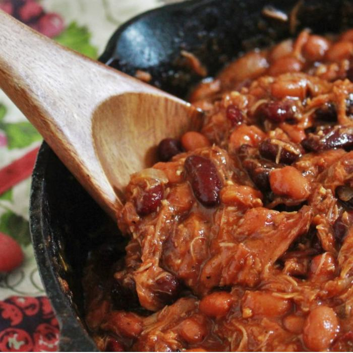 pork belly bourbon baked beans in a cast iron skillet