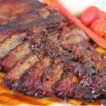 sliced brisket, topped with bacon barbeque sauce, served on a wood platter with sliced bell pepper and cherry tomatoes