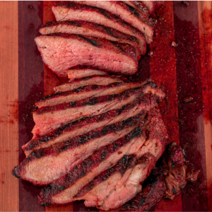 Sliced coffee rub tri tip on a striped wooden cutting board.