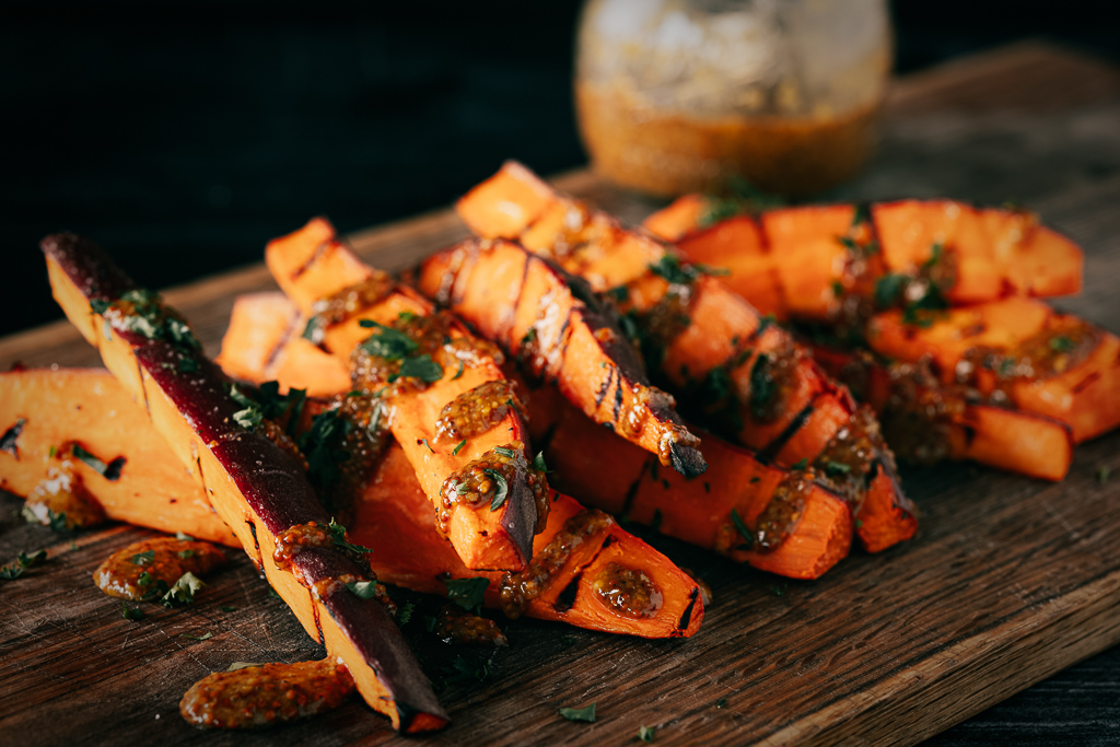 Grilled sweet potato fries drizzled with honey mustard on a wooden cutting board.