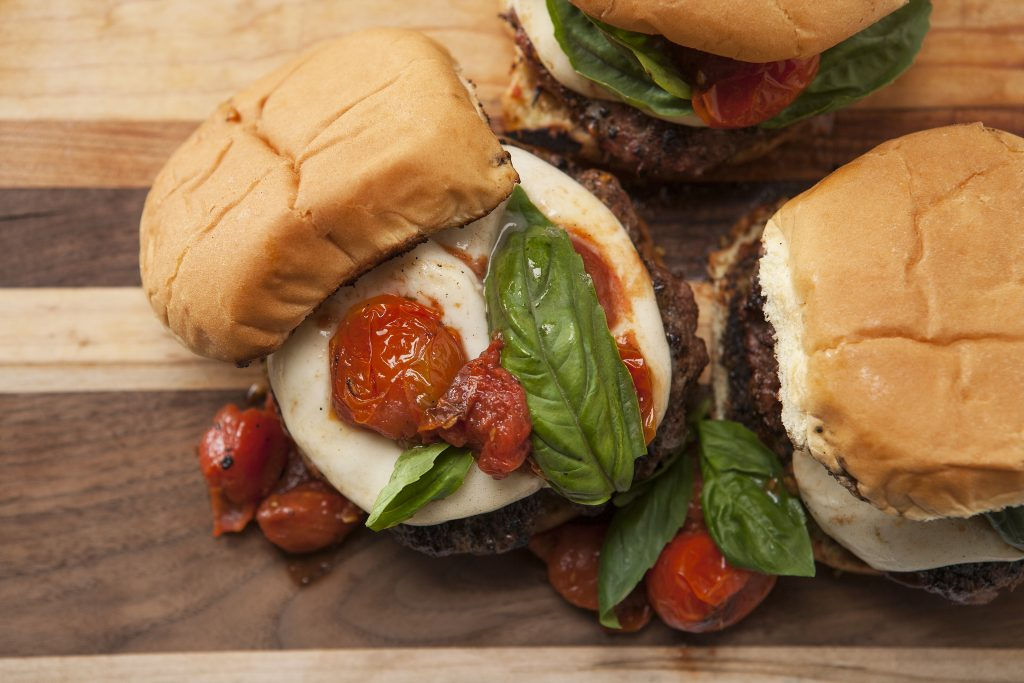Overhead view of garlic butter burger topped with mozzarella, tomatoes, and basil