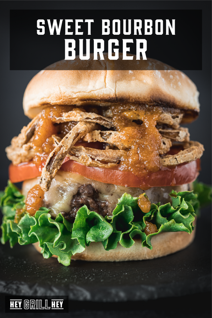 Bourbon burger topped with lettuce, tomato, crispy onion straws and bourbon BBQ sauce with text overlay - Sweet Bourbon Burger.