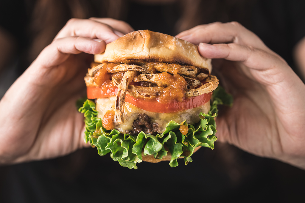 Two hands holding a fully loaded bourbon burger.