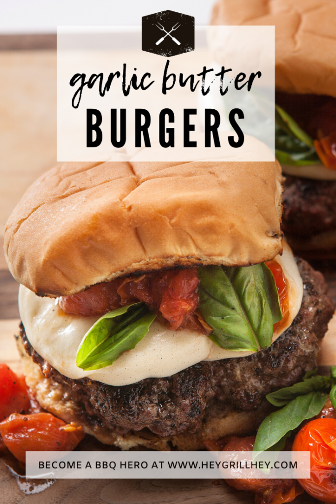 Garlic butter burgers topped with mozzarella, basil, and grilled tomatoes on a wood cutting board