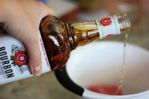 close up shot of a bottle of bourbon being poured into a white bowl