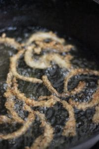 close up view of sliced, breaded onions in the shapes of straws being fried in oil