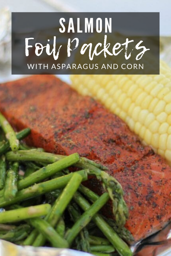 "Grilled asparagus, seasoned whole salmon, and an ear of corn on a sheet of aluminum foil with the text overlay: ""Salmon foil packets with asparagus and corn."""