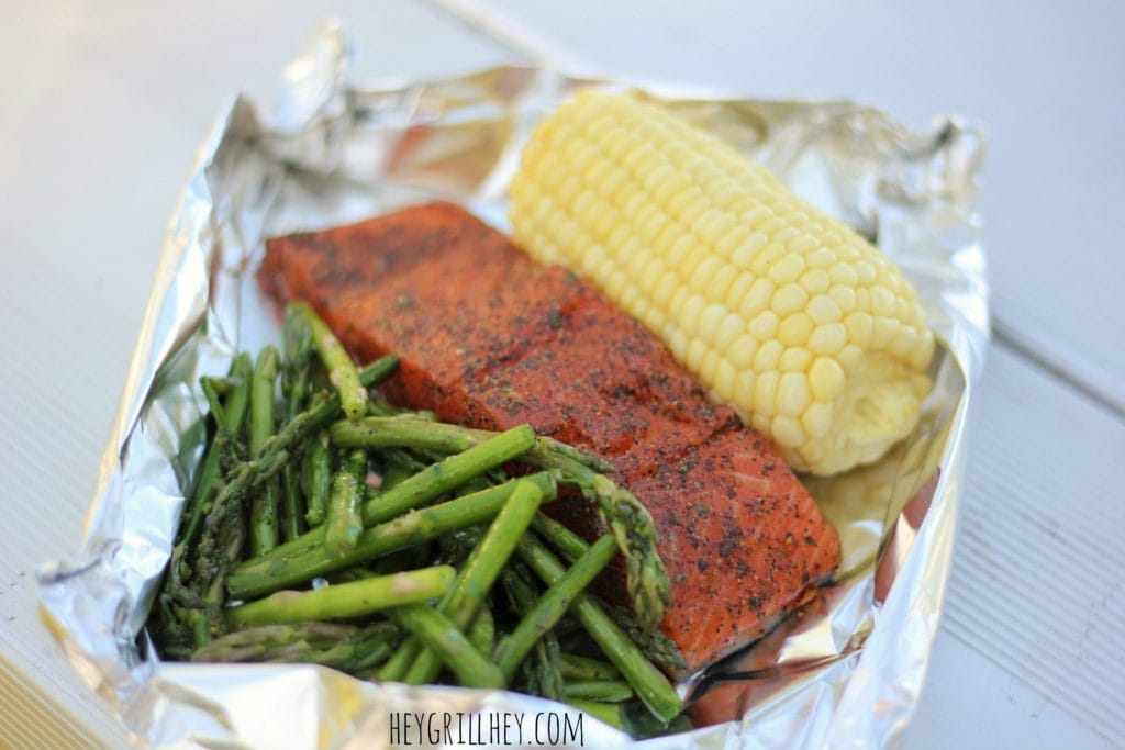 A pile of grilled asparagus, one whole seasoned, grilled salmon fillet, and a half ear of corn in a aluminum foil packet on top of a white table.