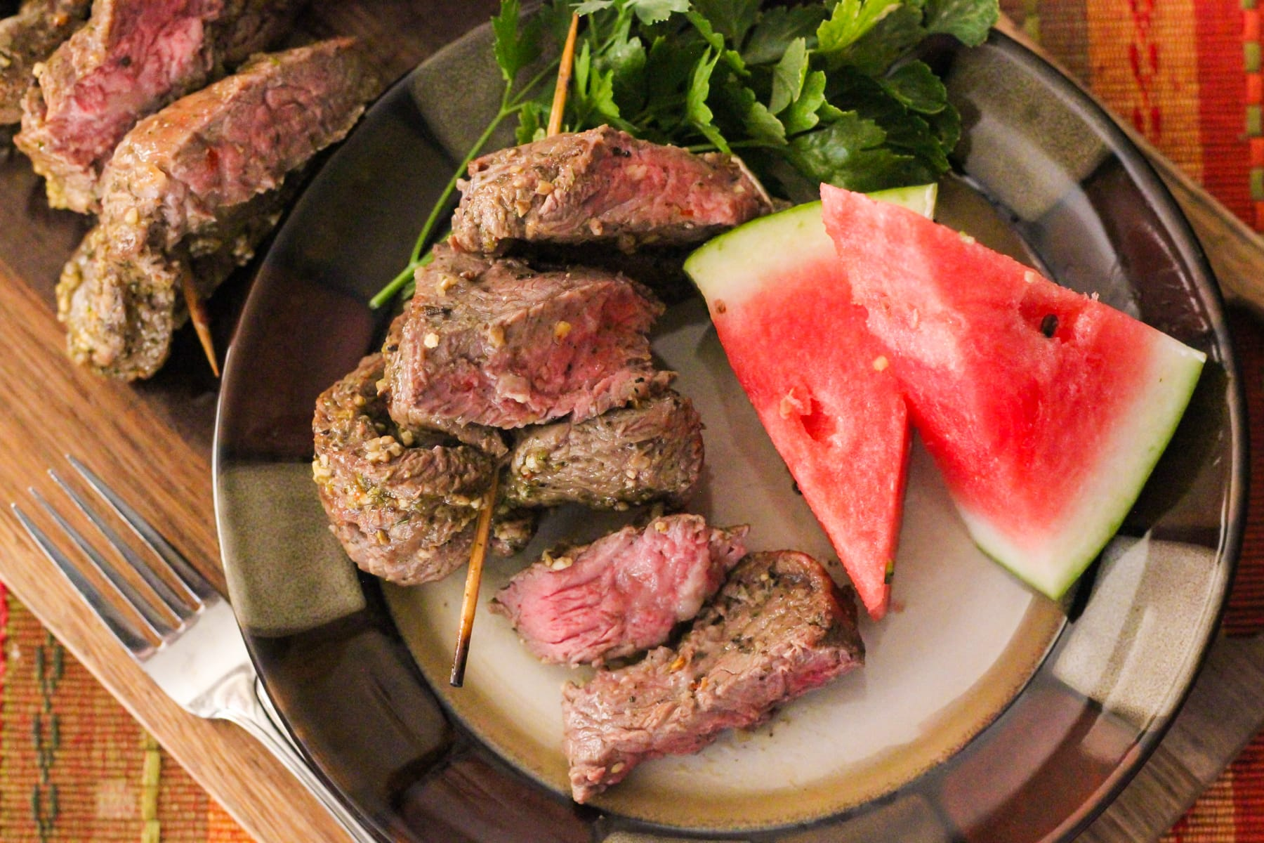 steak on a plate with watermelon slices.