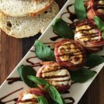 Aerial view of Bacon Wrapped Stuffed Grilled Tomatoes served in a single file line on a white dish with basil leaves and drizzled with balsamic vinegar