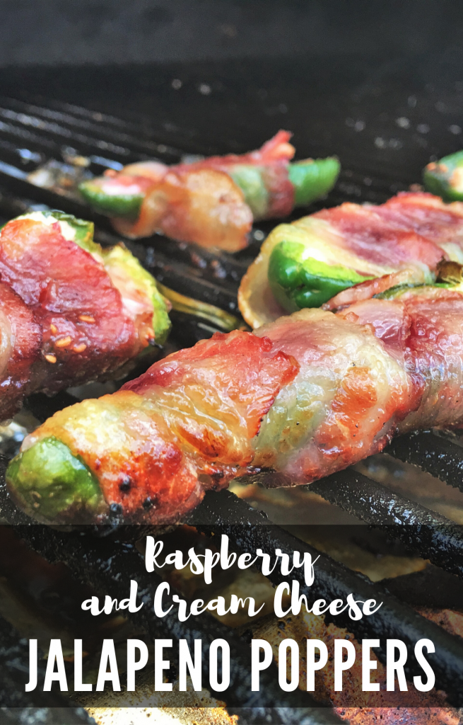 """Jalapenos sliced in half, stuffed with cheese and wrapped in bacon, spread out on the grill grate. Text overlay reads """"Raspberry and Cream Cheese Jalapeno Poppers."""""""