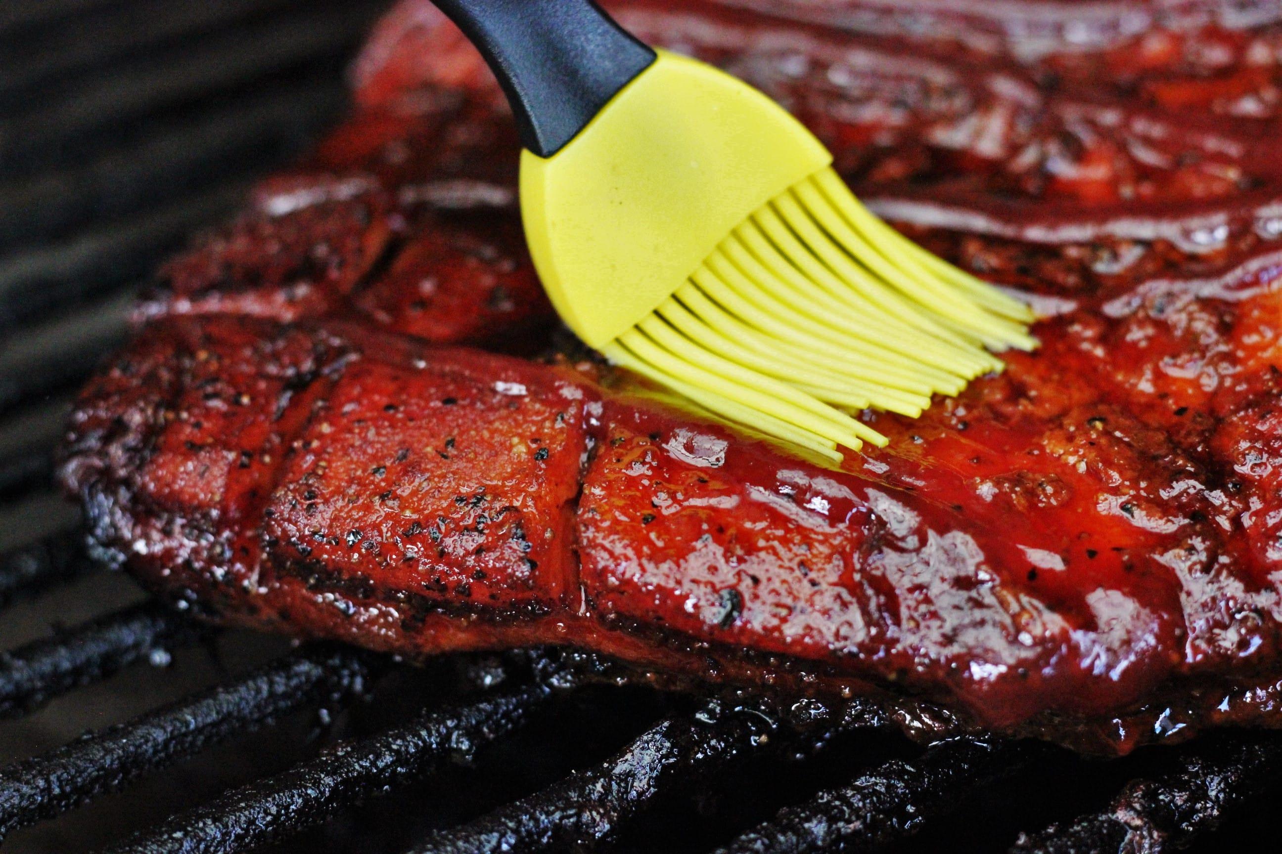 basting brush brushing BBQ sauce on smoked pork belly