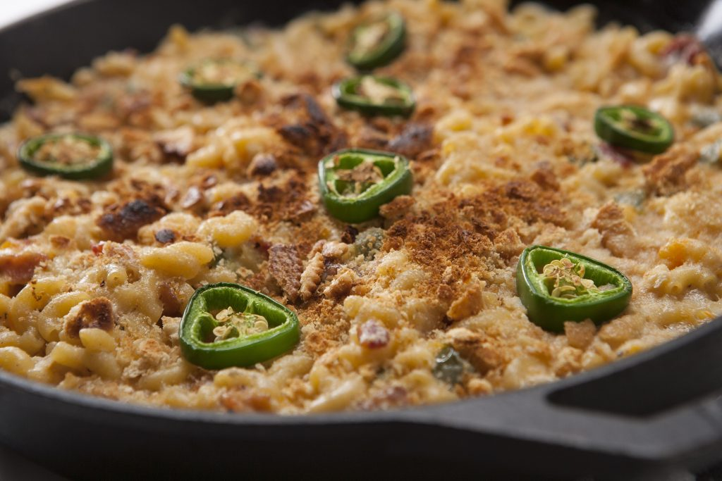 Smoked macaroni and cheese topped with toasted cracker crumbs and sliced jalapenos in a cast iron skillet