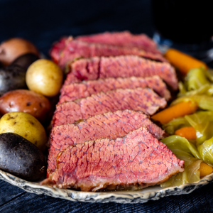 Slices of homemade corned beef lined up on a serving dish next to whole potatoes, cabbage, and baby carrots.